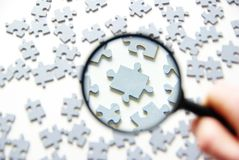 Magnifying glass and puzzle Royalty Free Stock Photo