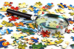 Magnifying glass and puzzle Royalty Free Stock Photography