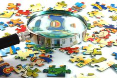 Magnifying glass and puzzle Stock Photo
