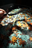 Magnifying glass, puzzle Stock Images