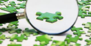 Magnifying glass on the puzzle. Magnifying glass on the green puzzle stock photo