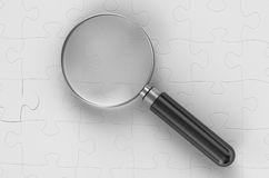 Magnifying glass on puzzles Stock Photography
