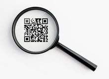 Magnifying glass with qr-code. Qr-code under a magnifying glass, with isolated background Royalty Free Stock Image
