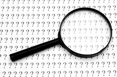 Magnifying glass and question marks. Looking for answers. Conceptual photo Royalty Free Stock Image