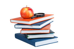 Magnifying glass and red apple on stack of books Royalty Free Stock Photos