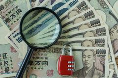 Magnifying glass and red combination lock pad on pile of japanes. E yen banknotes as financial safe haven or security concept Stock Photo