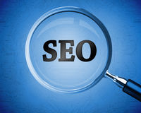 Magnifying glass revealing the word SEO Stock Photography