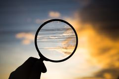 Magnifying glass scan clound and electric wire on sunset sky Stock Photo