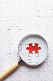 Magnifying glass search missing puzzle peace Royalty Free Stock Photo