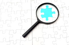 Magnifying glass searching missing puzzle peace stock photos