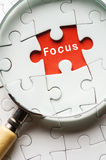 Magnifying glass searching missing puzzle peace FOCUS royalty free stock images