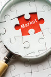 Magnifying glass searching missing puzzle peace MARKET Stock Photos