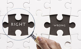 Magnifying glass searching missing puzzle peace Stock Photography