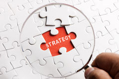 Magnifying glass searching missing puzzle peace STRATEGY Royalty Free Stock Photography