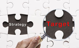 Magnifying glass searching missing puzzle peace Target Stock Images