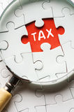 Magnifying glass searching missing puzzle peace TAX stock image