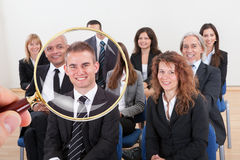 Magnifying Glass Selecting The Best Candidate For The Job. Person Holding Magnifying Glass On The Successful Businessperson For The Recruitment In Job Stock Photo
