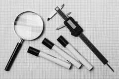 Magnifying glass, slide calipers and pens on a graph paper Royalty Free Stock Images
