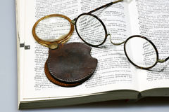 Magnifying glass and spectacles. On a dictionary Royalty Free Stock Photos