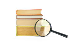 Magnifying glass beside a stack of books. Magnifying glass over the stack of books Royalty Free Stock Image