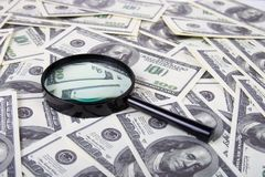 Magnifying glass on a stack of dollars Royalty Free Stock Images