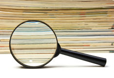 Magnifying glass and stack of magazines Royalty Free Stock Images