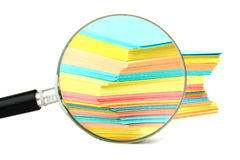 Magnifying glass and a stack of paper Royalty Free Stock Photo