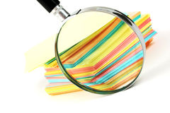 Magnifying glass and a stack of paper Royalty Free Stock Photography
