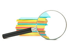Magnifying glass and a stack of paper Royalty Free Stock Images