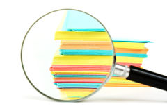 Magnifying glass and a stack of paper Stock Images
