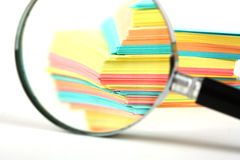 Magnifying glass and a stack of paper Stock Photos