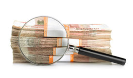 Magnifying glass and stack of rubles Stock Images