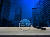 Business happy new year 2019 cover concept. Magnifying glass with 2019 text and graph on wooden table over number and modern office city tower, Business happy royalty free illustration