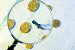 With a magnifying glass to observe the villain dolls and coins Stock Photo