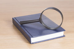 Magnifying glass on top of book. Elevated view of magnifying glass on top of book, wood table background Stock Images