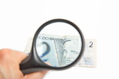 Magnifying Glass on the two Brasilian Reais.  Royalty Free Stock Photography