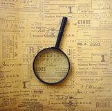 Magnifying glass on vintage newspaper background. royalty free stock photography