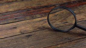 Magnifying glass on a vintage wooden table. Slider shot.