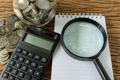 Magnifying glass on white paper and calculator with stack of coi Stock Photography