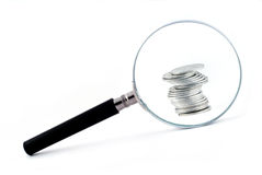 Magnifying Glass With A Column Of Coins Behind Royalty Free Stock Photos