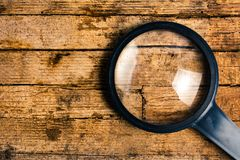 Magnifying glass on wood background isolated glass on wood background. Magnifying glass on wood background isolated stock photo