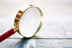 Magnifying Glass On Wood. Investigation concept. Magnifying glass closeup on wooden surface Royalty Free Stock Photos