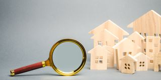 Magnifying glass and wooden houses. House searching concept. Home appraisal. Property valuation. Choice of location for the. Construction. Search for housing stock photo