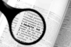 Magnifying glass on the word objectif (goal) in a dictionary Royalty Free Stock Images