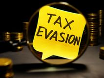 Magnifying glass and words tax evasion with money. Magnifying glass and words tax evasion with coins stock photos