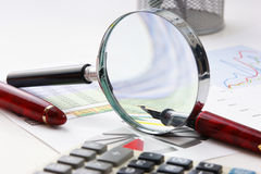 Magnifying glass and the working pape Stock Images