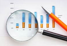 Magnifying glass and the working paper Stock Photo