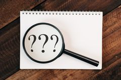 Magnifying glass zooming into question mark on notebook on a wooden table. Problem and research concept Royalty Free Stock Photo