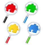 Magnifying glasses with puzzle pieces Stock Images