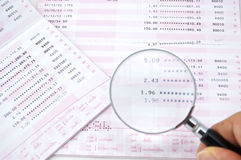 Magnifying interest. The man are magnifying the interest from pink and white bank account Royalty Free Stock Photography